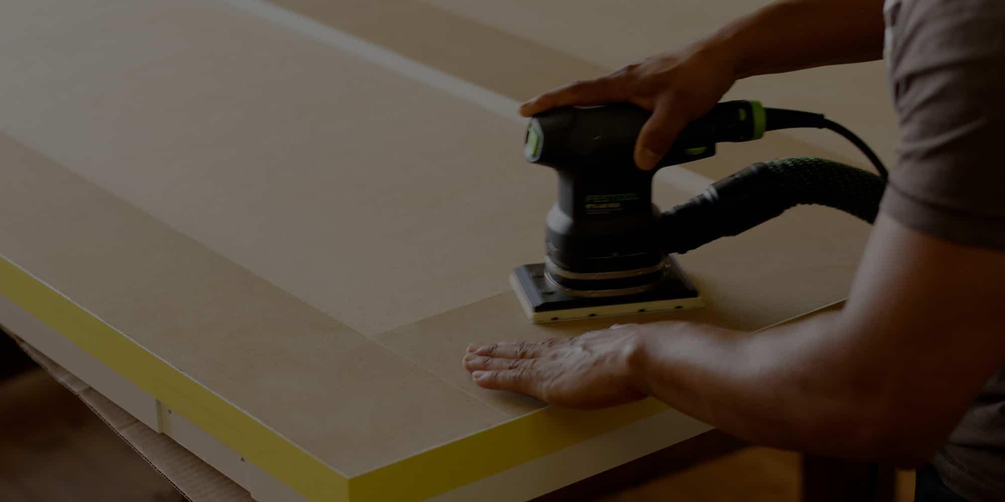 Man sanding board